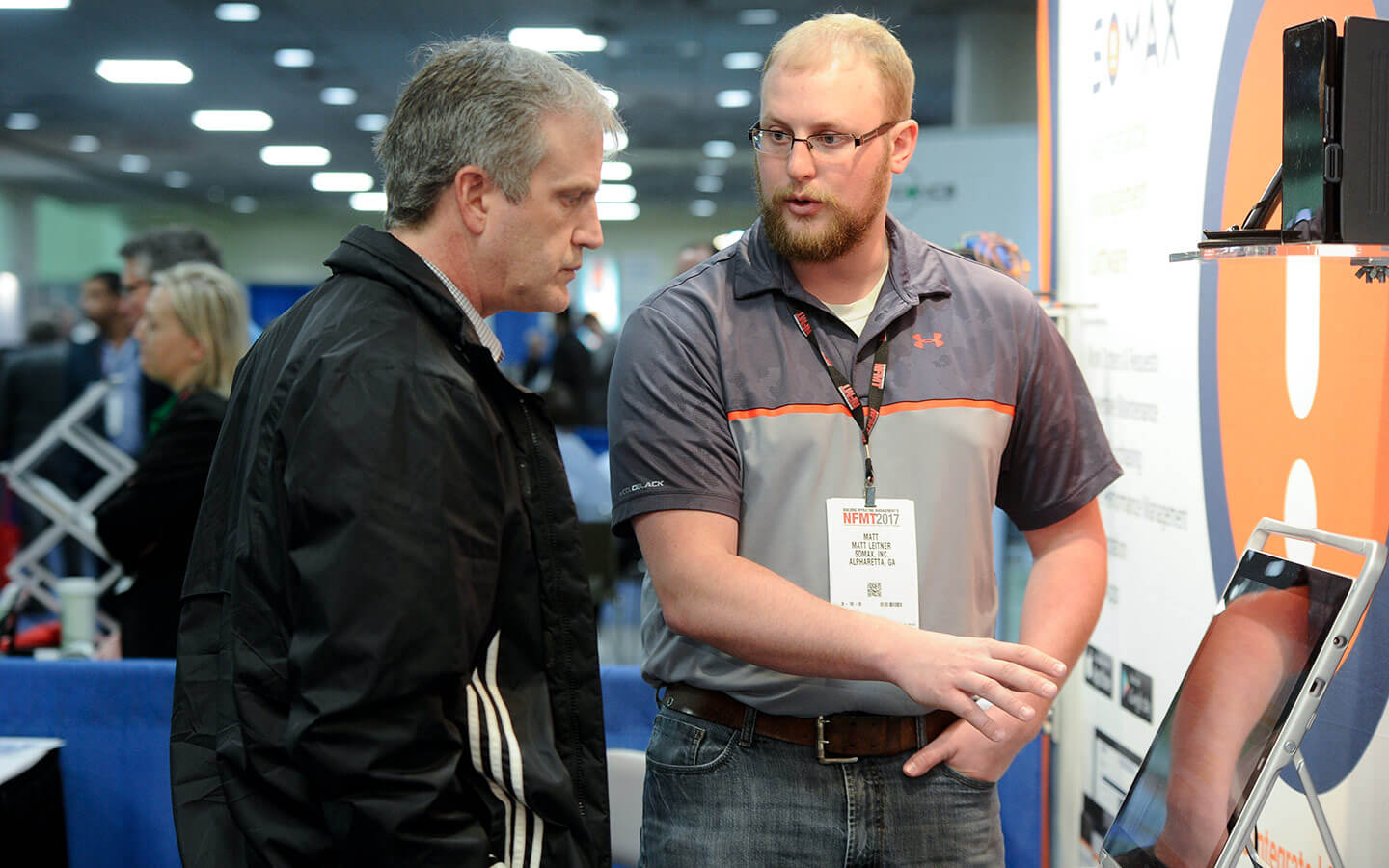 NFMT Exhibitor showing man a screen