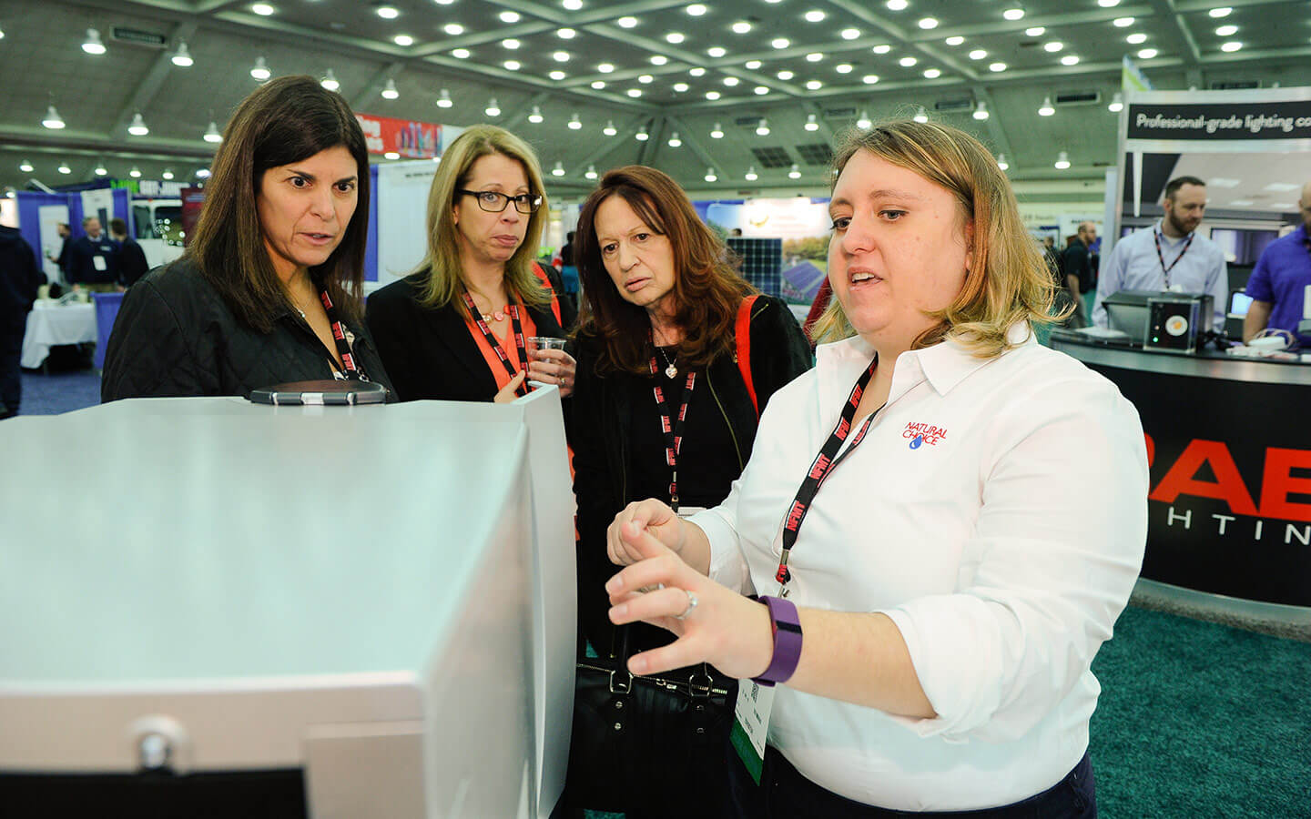 NFMT exhibitor showing product to group of women